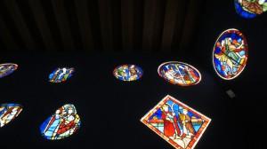 中世美術館の古ステンドグラス展示。中央上部は、「女性を誘惑する悪魔」の図。